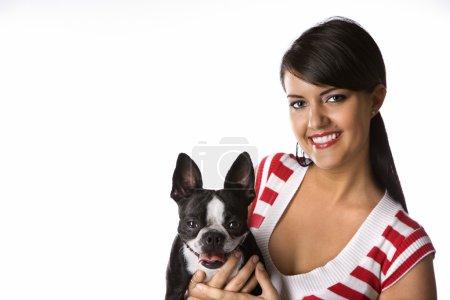 Woman holding Boston Terrier dog.