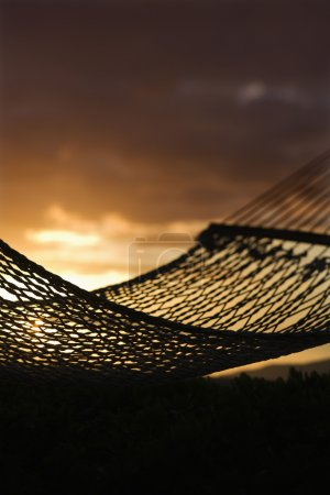 Hammock against Maui ocean sunset.