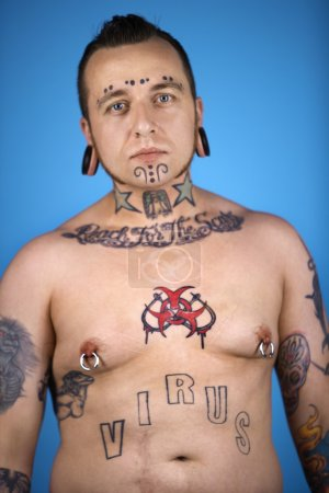 Man with tattoos and piercings.
