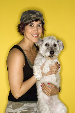 Smiling pretty woman holding dog.