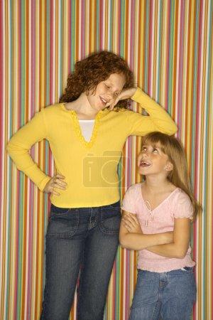Girl leaning on smaller girl.