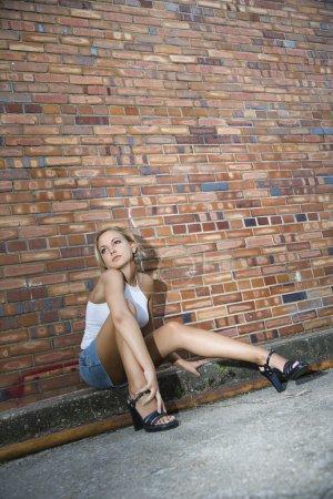 Woman against brick wall.