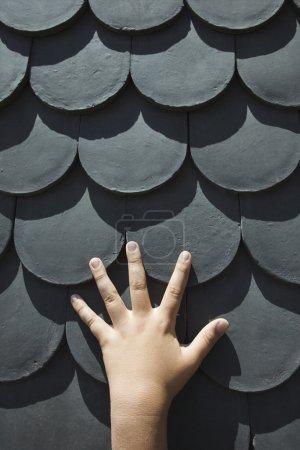 Photo pour Gros plan de la main du garçon caucasien sur le toit avec échelle en forme de bardeaux à Lisbonne, portugal. - image libre de droit