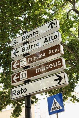 Photo pour Vue en angle bas du panneau de passage à niveau pour piétons et des panneaux directionnels à Lisbonne, Portugal. Plan vertical . - image libre de droit