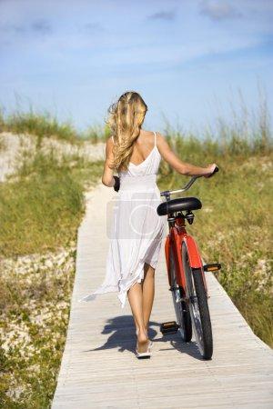 Photo pour Vue arrière de la jeune femme qui descend une promenade à vélo. Plan vertical . - image libre de droit