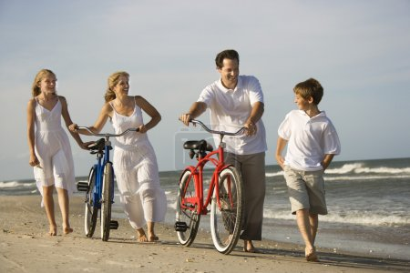 Photo pour La famille descend la plage alors que le père et la mère poussent leurs vélos. Plan horizontal . - image libre de droit