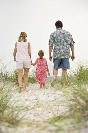 Photo for Caucasian mid-adult man and woman walking with female child toward beach. - Royalty Free Image