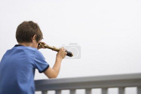 Boy looking through telescope.