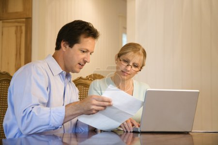 Husband and wife paying bills.