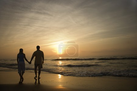 Photo for Silhouette of couple walking on beach at sunset holding hands. Horizontally framed shot. - Royalty Free Image