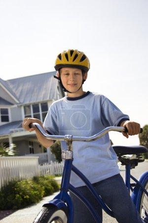 Photo pour Caucasien garçon pré-ado sur bicyclette portant casque regardant visionneuse. - image libre de droit