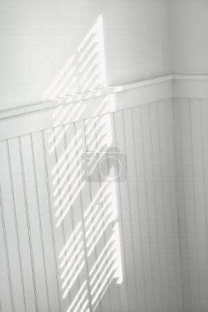 Sun through window blinds on wall.