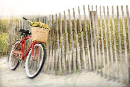 Foto de Bicicleta vintage roja con cesta y flores apoyado contra una valla de madera en la playa. - Imagen libre de derechos