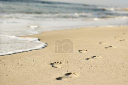 Photo pour Côte sablonneuse pittoresque avec empreintes de pas et vagues . - image libre de droit