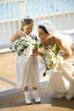 Photo for Caucasian mid-adult bride kneeling next to flower girl admiring her flowers. - Royalty Free Image