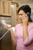 Serious woman on two telephones.