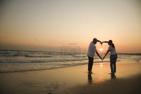 Photo pour Mid-adult couple en forme de coeur avec les bras sur la plage au coucher du soleil - image libre de droit