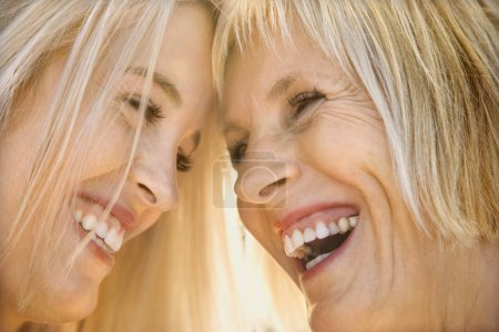Photo for Portrait of Caucasian mother and daughter laughing and looking at each other. - Royalty Free Image