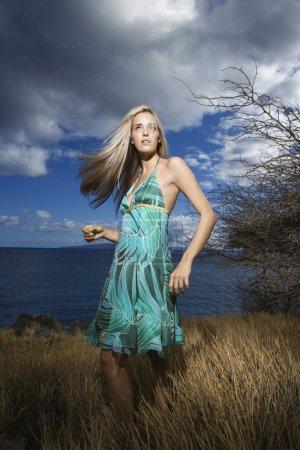 Photo pour Caucasien jeune adulte blonde femme debout dans le champ sur la côte avec les cheveux balançant . - image libre de droit