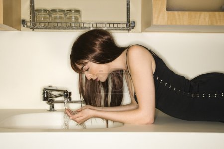 Photo for Pretty Caucasian young woman lying on kitchen counter drinking water from faucet. - Royalty Free Image