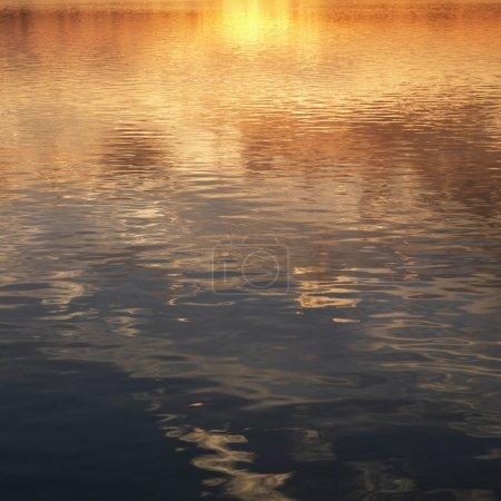 Photo pour Reflets du coucher de soleil orange et jaune sur l'eau. - image libre de droit
