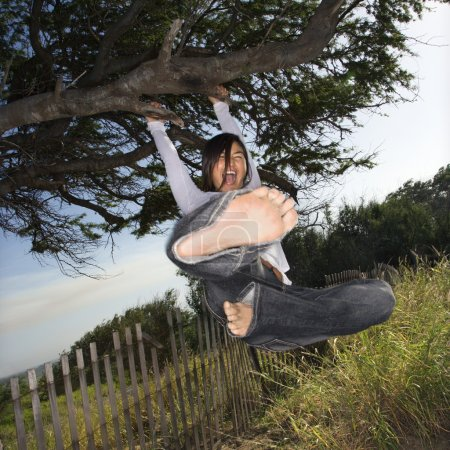 Photo for Young adult Asian female holding on to a tree and kicking towards viewer. - Royalty Free Image