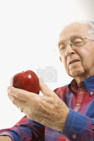 Caucasion elderly man looking at red apple in his hand.