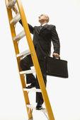 Businessman climbing ladder.