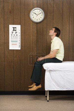 Photo pour Caucasien mid-adult male en attente sur la table dans le Cabinet du médecin rétro. - image libre de droit