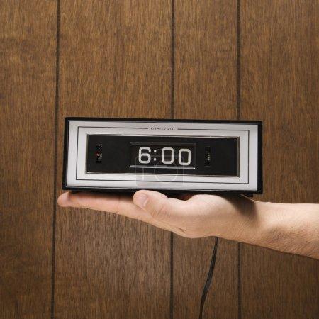 Hand holding alarm clock.