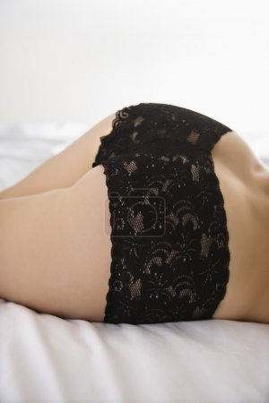 Back view of young woman wearing black lace pantie...