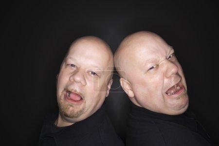Photo pour Caucasienne chauve milieu jumeau adulte hommes debout dos à dos avec des expressions tristes en regardant visionneuse. - image libre de droit