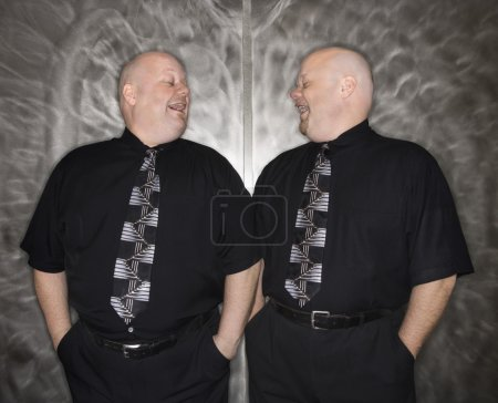 Twin bald men laughing.