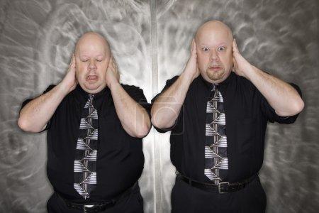 Twin men covering ears.