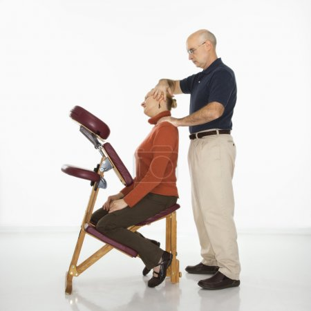 Photo for Caucasian middle-aged male massage therapist massaging neck of Caucasian middle-aged woman sitting in massage chair. - Royalty Free Image