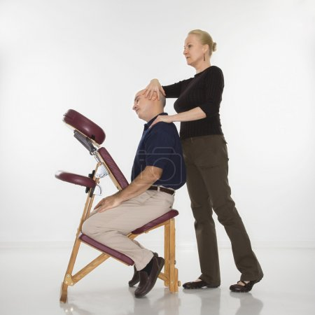 Photo for Caucasian middle-aged female massage therapist massaging neck of Caucasian middle-aged man sitting in massage chair. - Royalty Free Image