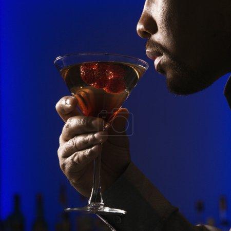 Photo pour Profil rapproché de l'homme afro-américain buvant du martini dans un bar sur fond bleu brillant . - image libre de droit