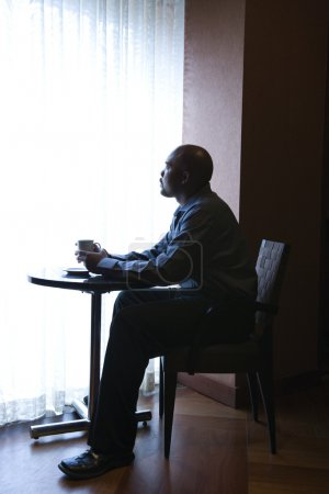 Photo for African-American businessman sitting down at a small cafe table next to a curtained window. He has a coffee cup in hand. Vertical shot. - Royalty Free Image