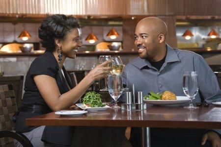 Photo pour Couple afro-américain dînant dehors. Ils grillent avec des verres de vin blanc et sourient. Plan horizontal . - image libre de droit