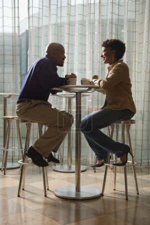 Photo pour Un homme afro-américain et une femme apprécient la compagnie des autres autour d'une tasse de café. ils sont assis à une table de petit café sur des tabourets. Défroissage vertical. - image libre de droit