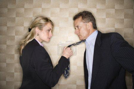Femme d'affaires en colère tirant cravate homme