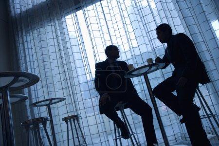 Foto de Incline la silueta de la vista de los empresarios asiáticos y afro-americanos sentado en una mesa tomando un café frente a una ventana. - Imagen libre de derechos