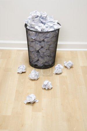 Photo pour Poubelle en treillis métallique pleine avec du papier froissé dispersé autour . - image libre de droit