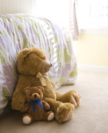 Photo for Plush brown teddy bears on bedroom floor. - Royalty Free Image