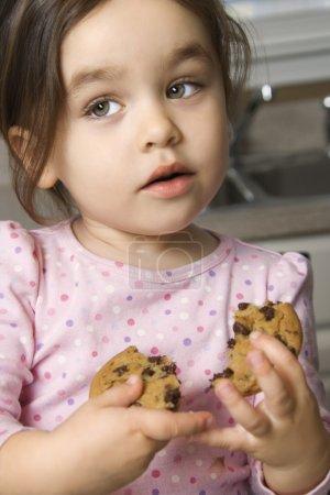 Girl eating cookie.