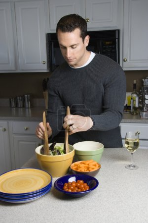 Photo for Caucasian man making salad on kitchen counter. - Royalty Free Image
