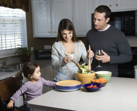 Photo for Caucasian woman making salad on kitchen counter with daughter and husband. - Royalty Free Image