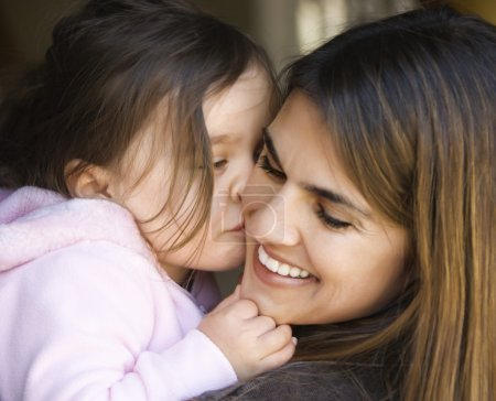 Photo for Caucasian mother holding daughter kissing her cheek and smiling. - Royalty Free Image