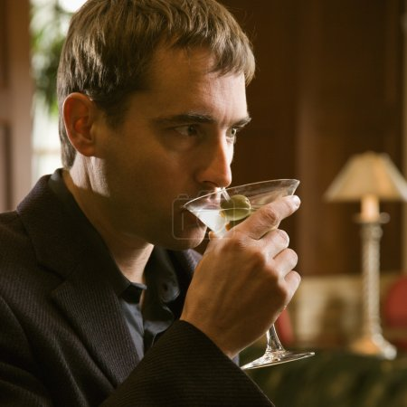 Photo for Mid adult Caucasian man drinking martini. - Royalty Free Image