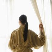 femme regardant dehors la fenêtre